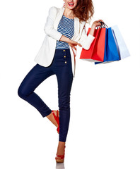 Smiling young woman with shopping bags on white background