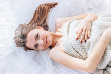 Portrait of a beautiful young girl on a white bed