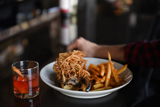 Person sitting at bar counter with cocktail and bowl of food