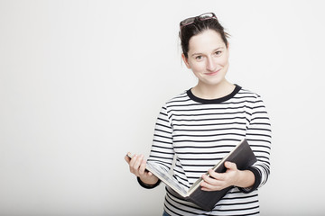 Young attractive smiling woman with glasses on head, standing with a magazine in their hands on a blank gray wall background in a striped sweater