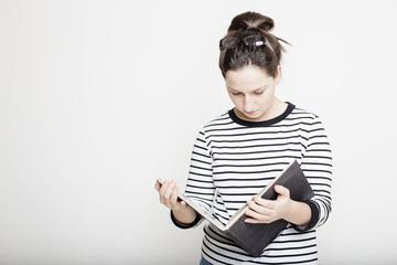 Young attractive smiling woman with glasses on head, focused reading magazine in their hands on a blank gray wall background in a striped sweater