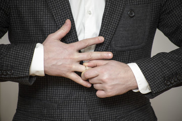 a man in a buttoned jacket struggling to remove wedding ring from his finger