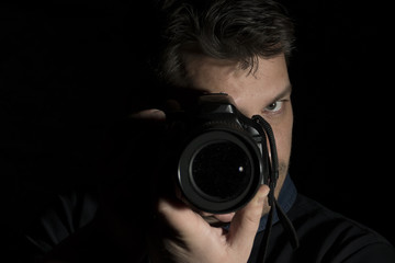 Young man as a photographer portrait isolated on black background