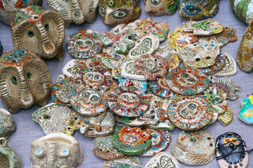 Many clay figurines of various shapes and different colors lying on the table. There are abstract shapes.