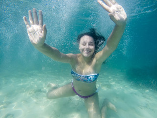 Underwater woman portrait at sand sea bottom