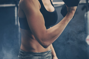 Woman at the gym focused on fitness, body shows muscle.  Good for exercise and health background.