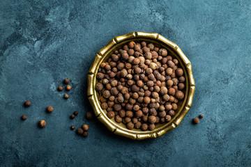 Fototapeta Allspice pepper, peppercorns on dark culinary background, top view, copy space obraz