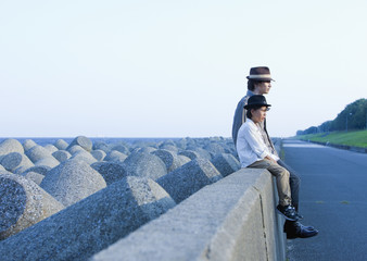 Father and son sitting on breakwater