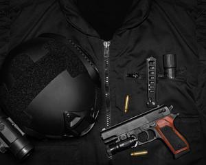 Photo of a tactical helmet, gun shells, hand gun, knife & flashlight  laying on a black swat vest.