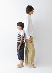 Father and son standing back to back