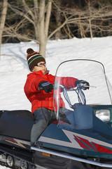 A boy riding on snowmobile