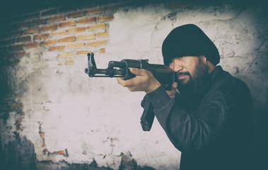 terrorist in black uniform and mask with kalashnikov