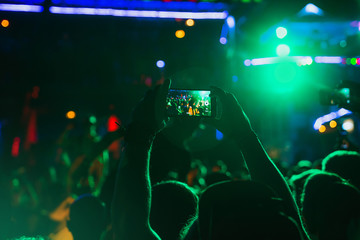 Video recording of the concert on the smartphone at the party. Silhouettes of concert crowd in front of bright lights on the background of a youth party.