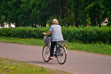 old woman riding a bicycle in the park