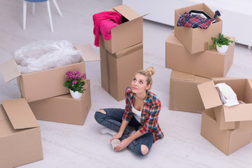 woman with many cardboard boxes sitting on floor