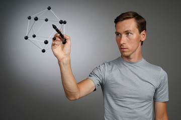 Young man works with a model of molecule.