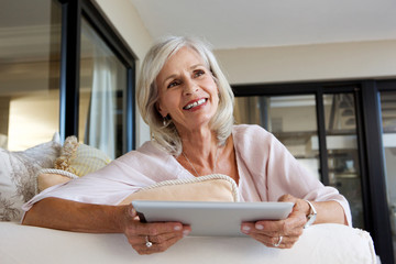 happy woman with touch screen tablet at home