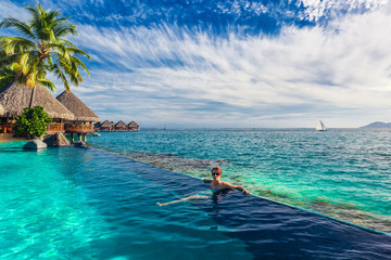Woman in the infinity pool in exotic island resort with bunalows over water