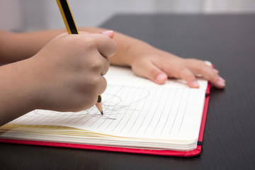 Close of children hands writing on excercise book