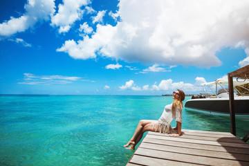 Woman enjoyong sun, sitting on pier with legs in water