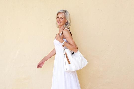 happy older woman in summer dress walking with purse