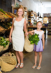 Portrait of woman and kid buying greens
