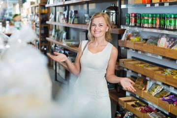 Smiling  woman standing among shelves