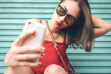 Asian woman holding smartphone digital camera with her hands and taking a selfie