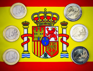 Spain cash money. Spain flag as a background. Three one euro coins and three tow euro coins on the Spanish flag. Macro image.