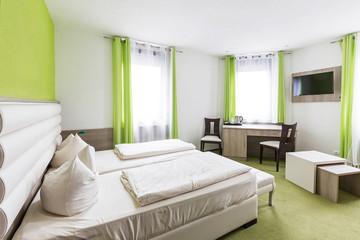 Hotelzimmer mit Doppelbett und Schreibtisch