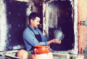 satisfied male with black-glazed ceramic vase standing close to kiln
