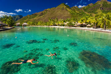 Young couple snorkeling over reef next to resort on an island