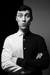 Low key portrait of a man in different shirts in black and white.