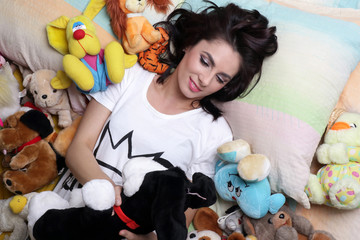 Woman like a child in her bed playing with soft toys