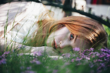Beautiful redhead sleepy young woman lying in the grass in a purple flower field