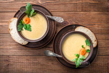 Pea soup in the bowl  on a  rustic wooden background .