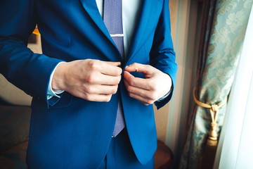 Closeup of man buttoning his jacket, business clothing concept