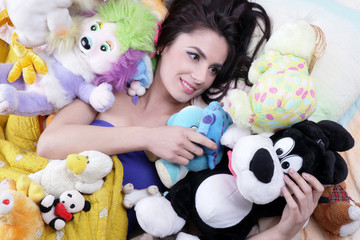 Woman feelings good with her soft toys like a child in her bed