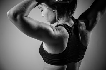 Beautiful female fitness model ready to start training in a studio with edgy lighting