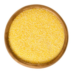 Cornmeal in wooden bowl. Raw uncooked meal, medium ground from dried maize. Common stable food. Boiled cornmeal is called polenta. Isolated macro food photo close up from above on white background.