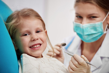 Small girl curing teeth in dentist office. Concept of milk tooth inspection and treatment.