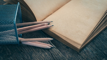 Pencils in storage basket lean against old book - split toning effect