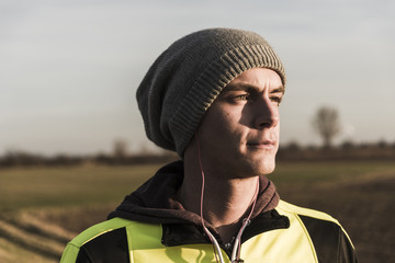 Portrait of athlete wearing wooly hat and earphones