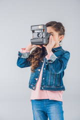 Adorable girl taking pictures on retro camera on gray
