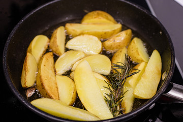 Potato slices fried in oil in a frying pan with rosemary