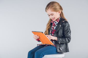 Cute smiling girl sitting on stool and using digital tablet