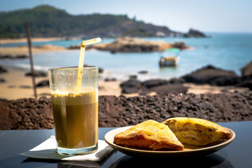 Breakfast on the beach. A sandwich and a coffee cocktail on the table in the restaurant on background of the sea