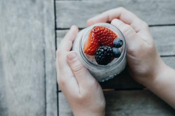 Boy hands with Pudding with chia seeds, yogurt and fresh fruits: Strawberries, blueberries and blackberries in glass jars on wooden background