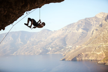 Young man trying to reach cliff in order to continue climbing challenging route. Rock climber pulling himself up and creating rope slack so that belayer could pull in excess rope.