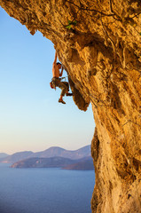 Rock climber on challenging route at sunset